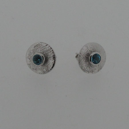 2018_Silver-blue-topaz-stud-earring, Convex  silver disc mounted with a round blue topaz and rhodium plated. Approximately 10mm diameter. Rhodium plated and hallmarked.