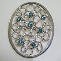 Blue topaz & silver coat brooch, Textured silver brooch set with seven 4mm blue topaz.