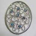Blue topaz & silver coat brooch, Textured silver brooch set with seven 4mm blue topaz.